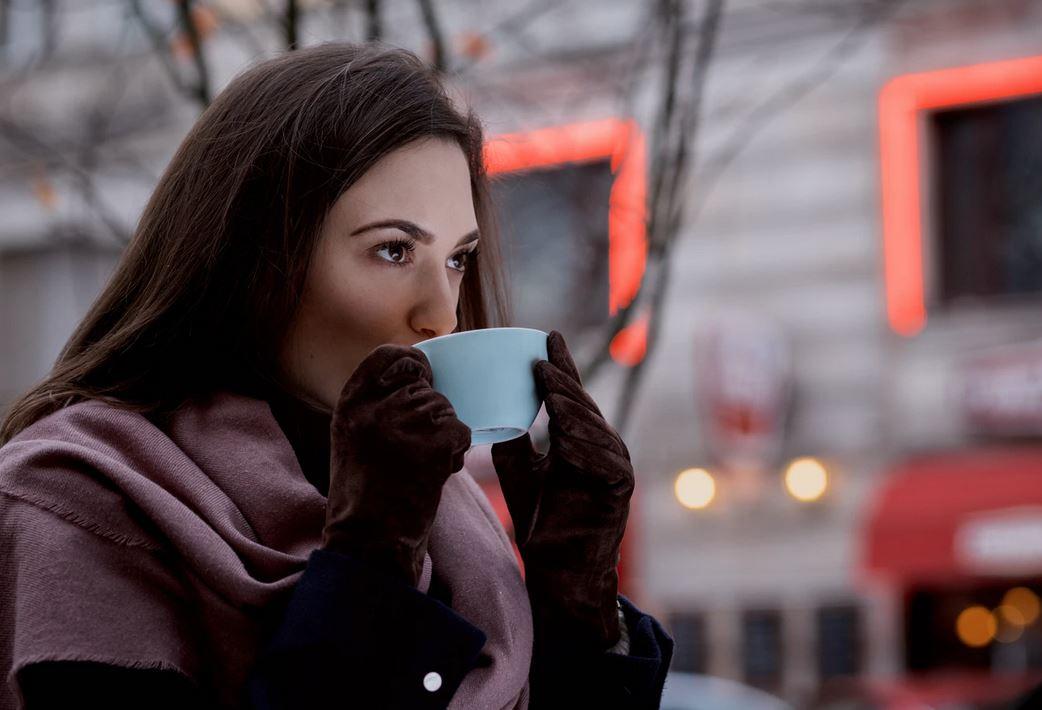 femme buvant un thé avec des gants en cuir